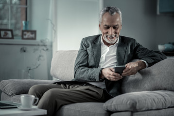 Joyful mood. Cheerful businessman keeping smile on his face while sitting on cozy sofa in living-room