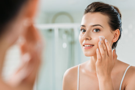 selective focus of smiling young woman applying face cream and looking at mirror in bathroom