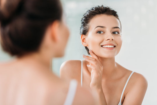 beautiful smiling young woman touching skin and looking at mirror in bathroom