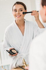 smiling young woman in bathrobe looking at mirror and applying makeup