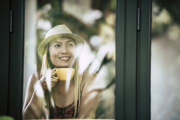 Happy young woman with latte coffee in morning