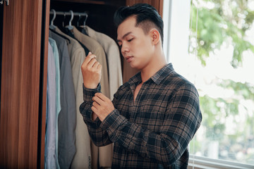 Young handsome Asian man buttoning shirt sleeves while dressing near wardrobe at home