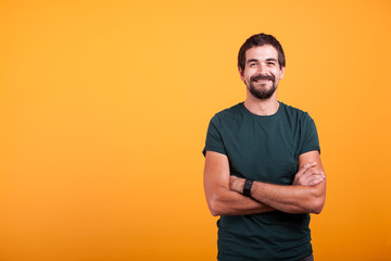 Handsome man with his arms crossed smiling at the camera isolated on yellow background. Portrait of attractive bearded confident person in studio photo Wall mural