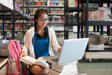 Content casual schoolgirl with stack of books in library using laptop and studying