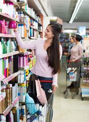 Smiling young woman pushing shopping trolley
