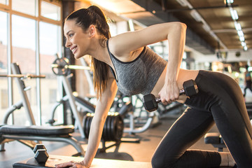 Side view of happy sporty girl lifting dumbbells on bench in gym