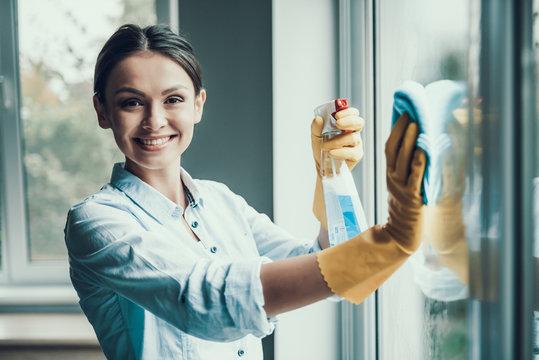 Young Smiling Woman Washing Window with Sponge