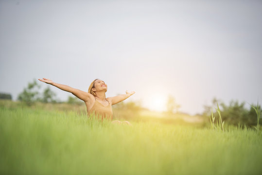 Young woman sitting feel good in grass field.