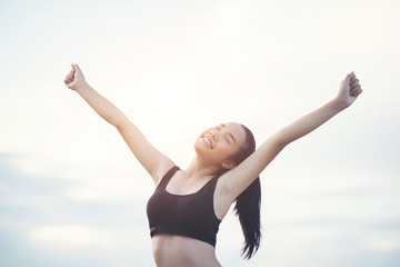 Happy smiling athletic woman with arms outstretched