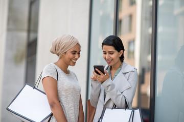 Muslim friends using a smartphone on a shopping trip