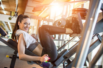 Sportive girl using weights machine for legs at the gym