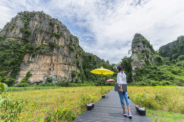 The women relaxed and enjoying the nature at Noen Maprang of Phitsanulok district,Thailand  in mountains with exciting view of  mountainous, back view.Traveler and holidays, Backpacker concept.