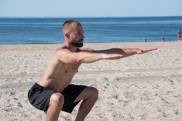Young athletic man exercising on beach during warm summer day. Squat sit stregth training to activate core and leg muscles holding arms straight out.