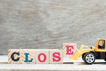 Toy bulldozer hold letter block e to complete word close on wood background