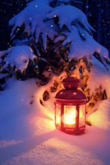 Christmas lantern in the woods under the tree. Lantern with a candle on Christmas eve.