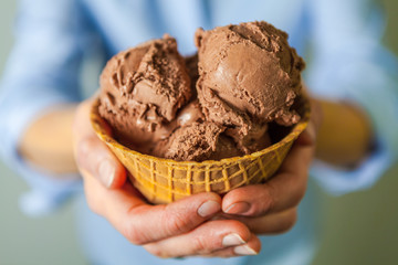 Closeup of Hands Holding a Waffle Bowl with Chocolate Ice Cream