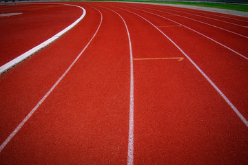 Red running track in the stadium.white line and Green lawn