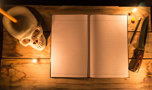 Human skull with candle light and notebook with pencil and knife on wooden table, Decorated for Halloween Theme with copy space.