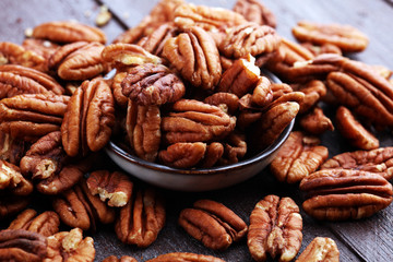 Stores photo Graine, aromate Pecan nuts on a rustic wooden table and pecan nuts in bowl