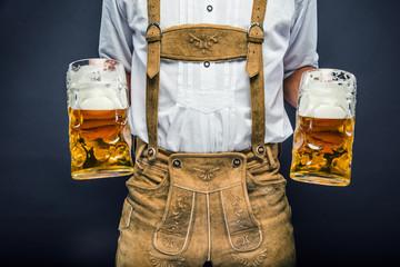 Mann in Lederhosen mit Oktoberfest-Bier