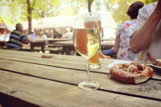 Food pause and relax at Bavarian beer garden, with pretzel,  a wine glass or a beer