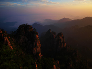 Monkey watching the sea of clouds in Huangshan (Yellow mountains) in China during sunrise