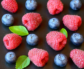 Fresh organic raspberries and blueberries on a dark background.Blueberry and raspberry.