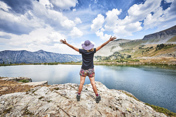 a young woman standing on top of a mountain with arms raised in excitement