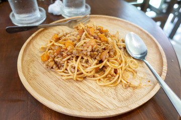close up of spaghetti on wooden dish