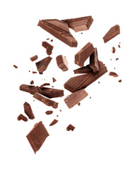 Pieces of dark chocolate falling close up on a white background