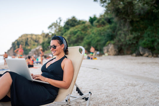 Beautiful woman working from the beach.