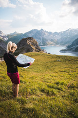 Girl Exploring Mountains and Navigating with a topographic Map next to a Alpine Lake