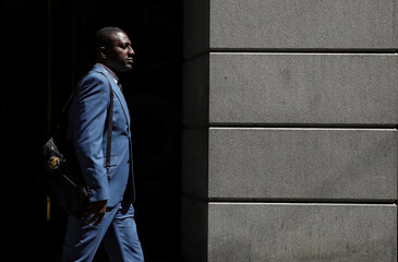 A man in a suit walks on Wall St. in New York