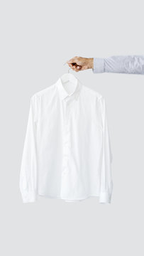 Male hand holding hanger with shirt