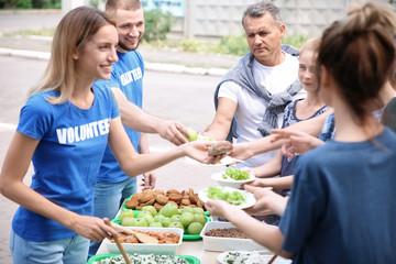 Volunteers serving food for poor people outdoors