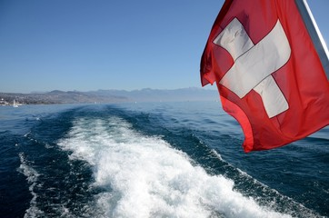 A Swiss flag floats in the wake of a boat from Lake Geneva