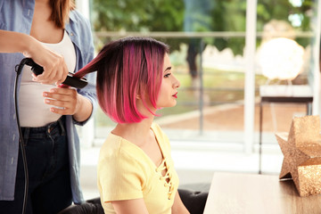 Professional hairdresser working with young woman in beauty salon. Trendy hair color