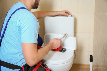 Plumber repairing toilet with wrench indoors, closeup