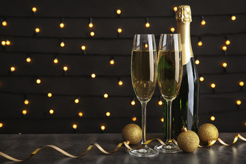 Glasses of champagne with bottle and festive decor on table against blurred fairy lights