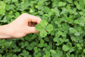 Woman holding four-leaf clover outdoors, closeup