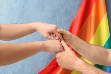 Gay couple holding hands near rainbow flag
