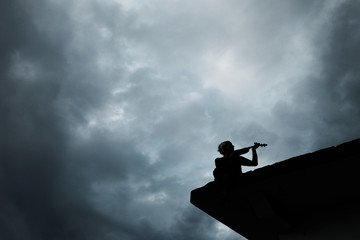 A silhouette of young girl playing on a musical instrument or violin on the roof of a house view from below