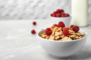 Bowl with cornflakes and raspberries on gray table. Whole grain cereal for breakfast