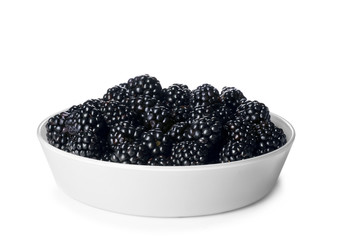 Bowl with ripe blackberries on white background