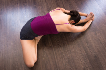 Woman in janu sirsasana from top on wood planks floor. Female yogi on head to knee forward bend. Lady practices yoga. Sitting posture, spinal twist, stretching concepts