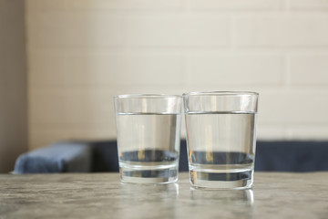 Glasses of water on grey table indoors