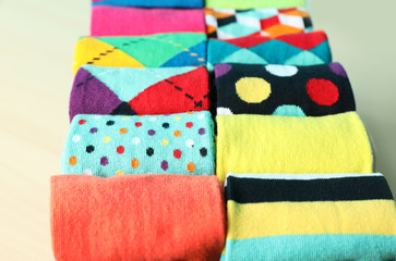 Fototapete - Rolled colorful socks on light background, closeup