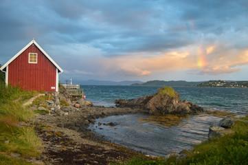 Blick auf Fjord mit roter Hütte; Harstad, Norwegen