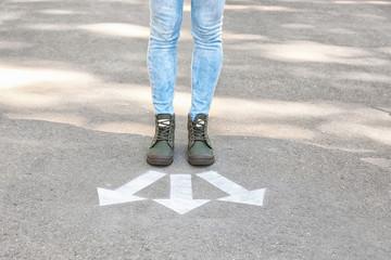 Woman standing near arrows on asphalt. Choice concept