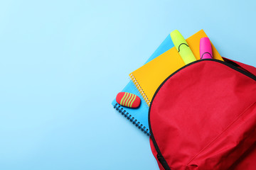 Flat lay composition with backpack, school stationery and space for text on color background
